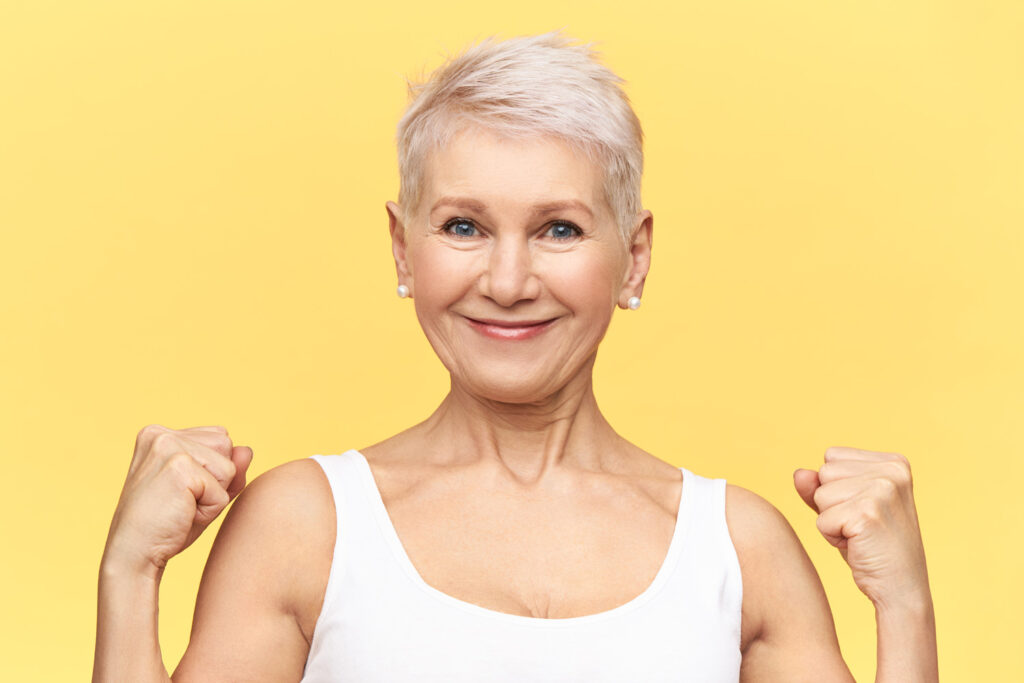 strong-positive-middle-aged-woman-with-dyed-short-hair-clenching-fists-showing-biceps-posing-isolated-blonde-mature-female-having-confident-proud-look (1)